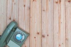 Retro rotary telephone with cable on wood table, wooden backgrou Royalty Free Stock Image