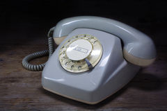 Retro rotary telephone of gray plastic with rotary dial on a dar Stock Photography