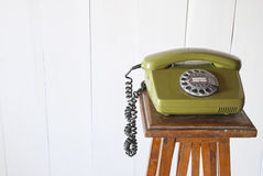 Retro rotary telephone on wood vintage table. White background Stock Photography