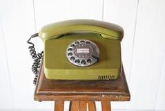 Retro rotary telephone on wood vintage table. White background Stock Photos