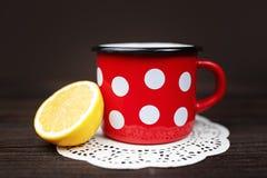 Retro- rote Tasse Tee mit Zitrone auf dem hölzernen Hintergrund Lizenzfreie Stockbilder