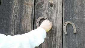 Retro rusty horse shoe hand hanging old wooden rural house wall stock video