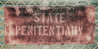 Retro Rusty Prison Sign. Retro Filtered Photo Of Rusty Grungy Old Penitentiary Prison Sign On Chain Link Fence Royalty Free Stock Images
