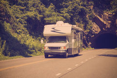 Retro RV Camper. Retro filter style image of RV camper driving down highway with rock tunnel stock photo