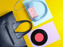 Retro 80s old fashioned objects. On a creative background. Headphones with audio cassette, lp record, women's leather bag. Top view. Flat lay royalty free stock photography