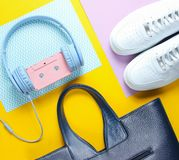 Retro 80s old fashioned objects. On a creative background. White sneakers, headphones with audio cassette, women's leather bag. Top view. Flat lay stock photos