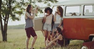 Retro 90 s przyjęcie przy natura przyjaciółmi pije wino i dobrego czas wpólnie, siedzący autobus retro pomarańczowy autobus zdjęcie wideo