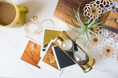 Retro 1970s Themed Still Life with Brass Hourglass Polaroids and Pyrex mug royalty free stock images