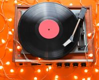 Retro 80s vinyl player. With bright glowing garlands on orange background. Top view, minimalism royalty free stock images