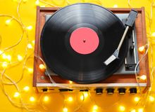 Retro 80s vinyl player. With bright glowing garlands on a yellow background. Top view, minimalism royalty free stock photo