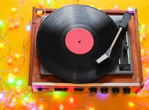 Retro 80s vinyl player. With bright glowing garlands on a yellow background. Top view, minimalism royalty free stock photos