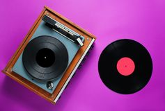 Retro 70s vinyl record player. With a vinyl record on a purple background. Top view, minimalism royalty free stock photography