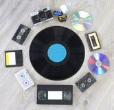Retro- Sache, Kamera, Film, Diskette, Vinylaufzeichnungsdiskette, Audiokassette und CD Stockfotografie