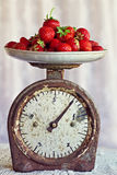 Retro scales with fresh ripe strawberries. Retro scales with a handful of fresh ripe strawberries Royalty Free Stock Images
