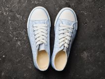 Retro scarpe da tennis alla moda da 80s su un pavimento di calcestruzzo nero Fotografie Stock Libere da Diritti