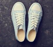 Retro scarpe da tennis alla moda da 80s su un pavimento di calcestruzzo nero Fotografia Stock Libera da Diritti