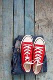 Retro scarpe da tennis e jeans rossi su un fondo di legno blu Immagine Stock