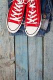 Retro scarpe da tennis e jeans rossi su un fondo di legno blu Immagini Stock