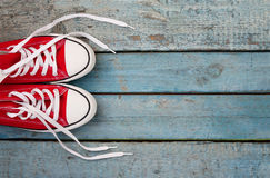 Retro scarpe da tennis rosse con le trecce sciolte su un fondo di legno blu Fotografie Stock Libere da Diritti