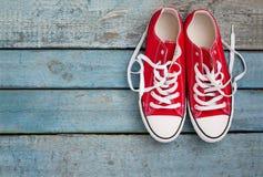 Retro scarpe da tennis rosse con le trecce sciolte su un fondo di legno blu Fotografia Stock Libera da Diritti