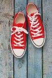 Retro scarpe da tennis rosse, primo piano, su un fondo di legno blu Fotografia Stock