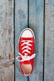 Retro scarpe da tennis rosse su un fondo di legno blu Fotografie Stock Libere da Diritti