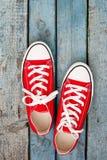 Retro scarpe da tennis rosse su un fondo di legno blu Immagini Stock Libere da Diritti
