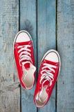 Retro scarpe da tennis rosse su un fondo di legno blu Immagini Stock