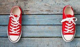 Retro scarpe da tennis rosse su un fondo di legno blu Fotografia Stock Libera da Diritti
