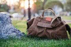 Retro scarpe marroni e borsa di cuoio dell'uomo nell'erba variopinta luminosa di estate nel parco Fotografie Stock