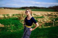 Retro- schauende Blondine mit der Sonnenbrille, die auf einem Gebiet steht Stockbilder