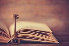 Retro- Schlüssel und geöffnetes Buch Stockfoto