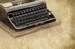 Retro- Schreibmaschine auf der alten Weinlese maserte Papierhintergrund Stockbilder