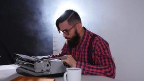 Retro schrijversconcept Jonge Gebaarde modieuze mens die op oude schrijfmachine schrijven stock video