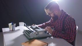 Retro schrijversconcept Jonge Gebaarde modieuze mens die op oude schrijfmachine schrijven stock videobeelden