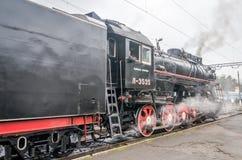 Retro- schwarze Lokomotive der alten Weinlese mit rotem Stern kam zu der Station, in der er fotografierte Passagiere und Touriste Lizenzfreie Stockfotos