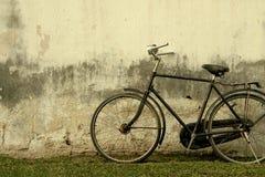 Retro- schwarzes Fahrrad gegen alte schädigende Gips-Wand - Weinlese-Effekt-Art-Bild stockfotografie