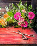 Retro scissors on red wooden table with flowers bunch Stock Photo