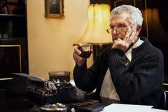 Retro scrittore dell'uomo senior con un vetro di whiskey Fotografie Stock
