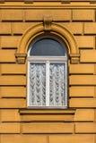 Retro se gammal gul fasadbyggnad med det välvda fönstret royaltyfria foton