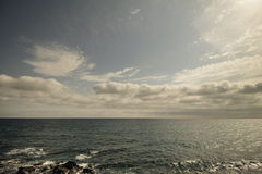 Retro seascape with cloudy sky. Royalty Free Stock Photo