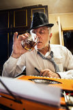 Retro Senior Man writer with a glass of whiskey. Retro Senior man, journalist, writer, writing on a traditional Typewriter. He is sitting with a glass of whiskey stock photo