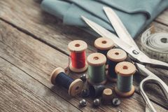 Free Retro Sewing Items - Tailoring Scissors, Thimbles, Buttons, Wooden Thread Spools, Measuring Tape And Green Fabric Royalty Free Stock Photo - 165691125