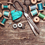 The retro sewing. Retro scissors, textile and sewing threads on the wooden table royalty free stock image