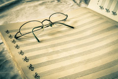 Retro Sheet Music. Vintage toned blank composition sheet music with eyeglasses Royalty Free Stock Image