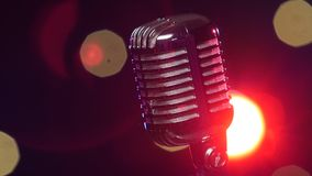 Retro shiny microphone rotating against blurry flashing lights. Close-up stock footage
