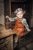 Retro shot of a smiling little boy. Pounding something in the tank Royalty Free Stock Photos
