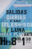 Retro signs for local ferry services, Titicaca lake, Bolivia. Vintage signs for local ferry services schedule written in Spanish and painted on old wall royalty free stock image