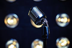 Retro silver microphone on spotlights blurred background. Close-up shot of retro silver microphone on spotlights blurred background. Microphone isolated on white stock images