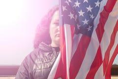 retro sj?lvst?ndighet f?r bakgrundsdaggrunge En kvinna med svart lockigt h?r rymmer en amerikanska flaggan Begreppet av v?rldsfre royaltyfri foto